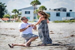 Young couple proposing on the quarterdeck beach