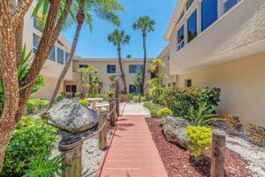 Vacation resort or Condominium with sidewalk having trees plants and windows